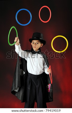 A young magician juggling colorful rings.  Some motion blur on the rings.