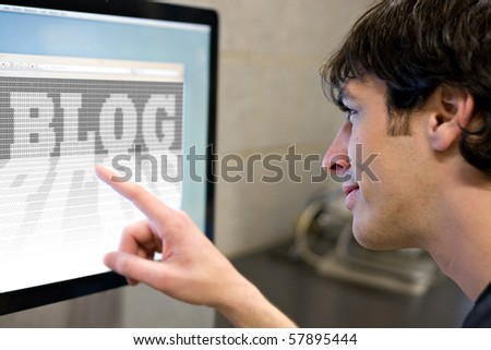 stock photo : A young main pointing at a computer screen that reads BLOG in the web browser window.