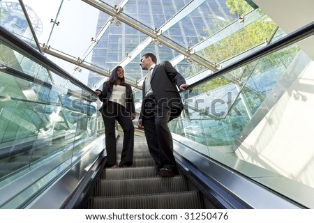A young make and female executive ride an escalator together in a modern hi-tech city setting