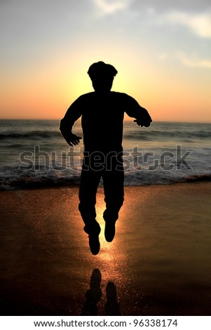 A young male adult jumping at evening on a beach with glowing sun and waves in the background