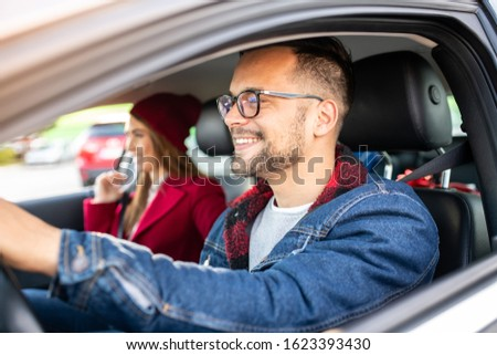A young male and a young female in a car, window-shot.