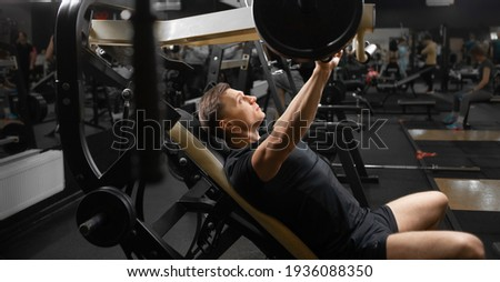 A young male athlete on the simulator in a sitting position shakes the muscles of his arms and chest. Training of muscle groups of the upper body. Trainings on simulators. ストックフォト ©