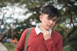 A young male call center agent or teacher tries to soothe his scratchy throat. Sore or dry throat caused by fatigue or disease.