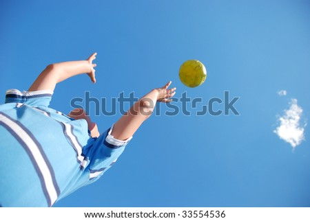 A young male child playing with the ball