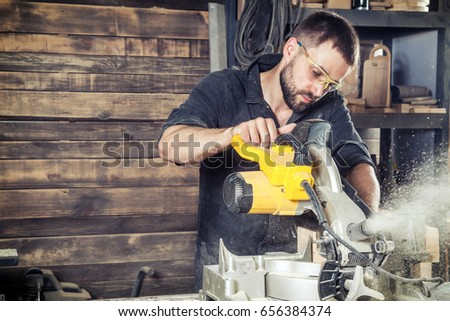 A young male construction carpenter saws a modern circular saw with a wooden board in the workshop, a wooden sawdust flying into the sides