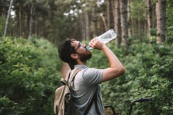 A young male cyclist drinks water from a plastic bottle at a halt in the forest. Tourism, active lifestyle.