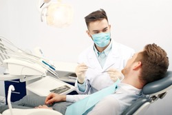 A young male dentist and a patient. Dentist office lifestyle scene. Doctor practice. Patient health care