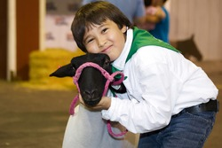 A young male 4-H agricultural club showman hugs his lamb while looking at the camera.