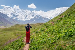 A young male hiker with a backpack in action of photographing the scenic beauty of snowcapped Lenin Peak in the base camp on the border of Kyrgyzstan and Tajikistan
