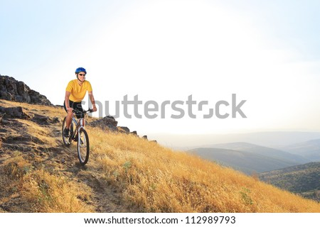A young male riding a mountain bike on a sunset, Macedonia - stock photo