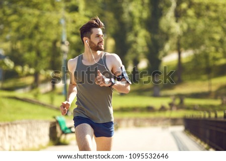 A young male runner jogs in the park #1095532646