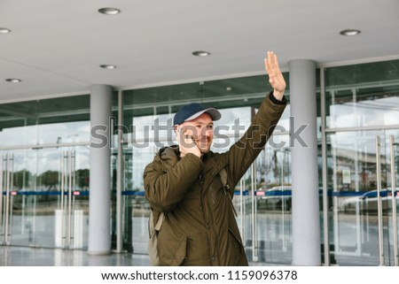 A young male tourist at the airport or near a shopping center or station calls a taxi or talks on a cell phone or communicates with friends using a mobile phone. #1159096378