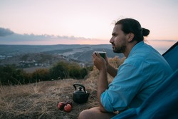 A young male tourist drinks tea near a tent in the mountains. A guy with a mug of hot tea in his hands sits under an awning of a tent on a hike alone in the mountains at sunset