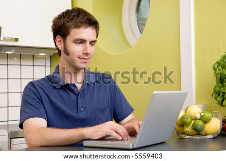 A young male using a laptop computer in the kicthen
