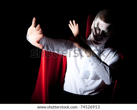 a young male vampire protecting himself from bright light