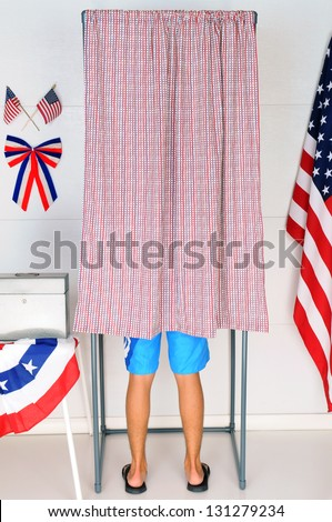 A young male voter inside a Voting Booth at his local polling place. Vertical format - man is unrecognizable.
