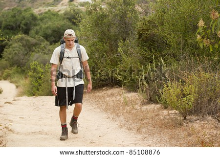 A young male walking on a mountain trail during a hiking trip.