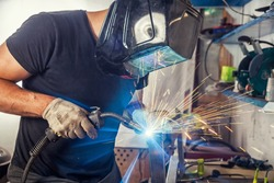 A young male welder in a black T-shirt, black welding mask and construction gloves weld a metal welding machine in the garage, in the background a lot of tools