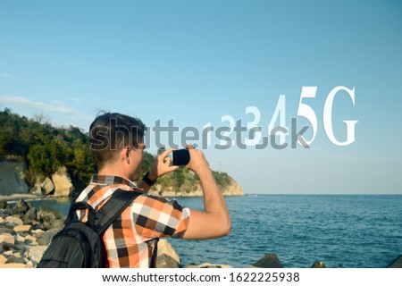 "A young man, a tourist with a backpack, explores new places and photographs the summer seascape, the inscription ""1, 2, 3, 4, 5G"", the concept of a broadband cellular network with worldwide coverage"