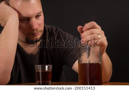 A young man alcohol abuse, on the table is alcohol