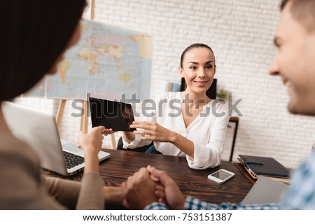 A young man and a woman came to the travel agency. They want to go on a trip during their holidays. The girl agent offers them different countries. She shows it on the tablet.