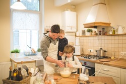 A young man and his children are preparing flavored cookies or pizza in a spacious white kitchen. Dad teaches his children to cook. Joint pastime with family.