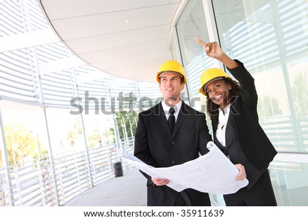 A young man and woman working on  construction site - stock photo