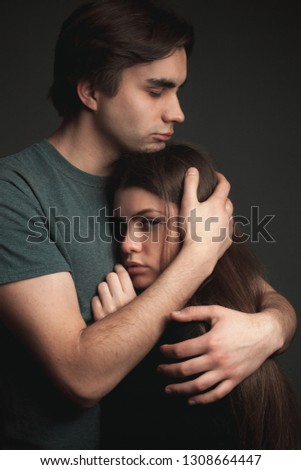 A young man and young woman are hugging. Low key