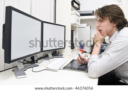 A young man at work behind a dual monitor work station in a design studio office environment