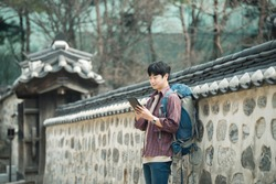 A young man backpacking in Korea. Using a tablet computer leaning against a wall
