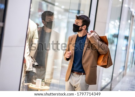 A young man carries shopping bags with a mask on his face, walks through shopping and looks at shop windows, life during a virus-caused pandemic