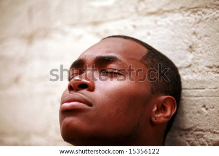 a young man closes his eyes while deep in thought