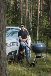 A young man cooks on a charcoal grill in a pine forest. The man leans against his crossover.