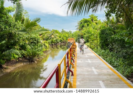 A young man cycles in Bang Krachao (Bang Kachao), along the moat and stilted pathway surrounded by lush tropical vegetation. Bang Krachao is known as the Green Lung of Bangkok.