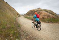 A young man cycling the Otago Central Rail Trail at Poolburn Gorge, South Island, New Zealand