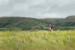 A young man cycling the Otago Central Rail Trail between Hyde and Middlemarch, South Island, New Zealand