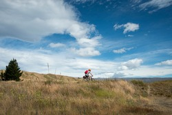 A young man cycling the Otago Central Rail Trail under the white clouds, at Chatto Creek, South Island, New Zealand