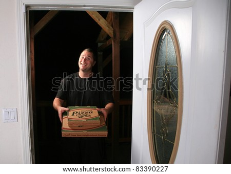 a young man delivers fresh pizza to your door. Pizza Delivery Man.