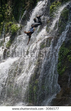 A young man dives off a waterfall in El Salvador