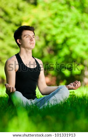 A young man doing yoga in the green park