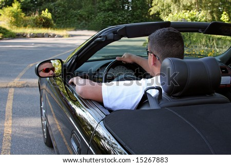 A young man driving away in his shiny black convertible.