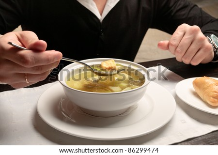A young man eating fish soup, sitting at a table elegantly served in a restaurant, close up