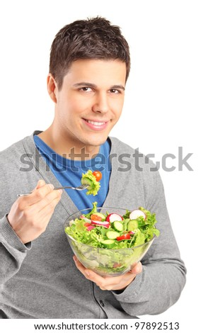 A young man eating salad isolated on white background