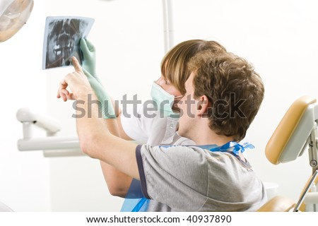 A  young man examining a panoramic radiography with his dentist.