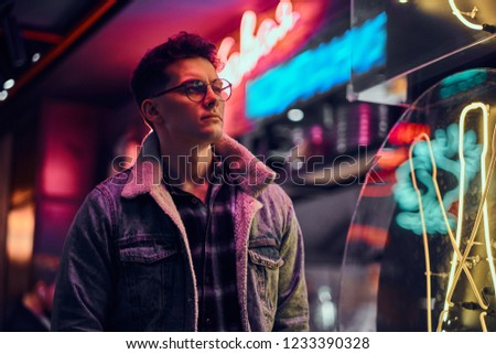 A young man fashionably dressed standing in the street at night. Illuminated signboards, neon, lights. #1233390328