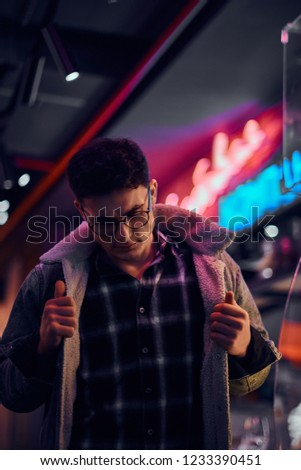 A young man fashionably dressed standing in the street at night. Illuminated signboards, neon, lights. #1233390451