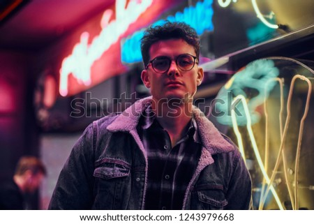 A young man fashionably dressed standing in the street at night. Illuminated signboards, neon, lights. #1243979668