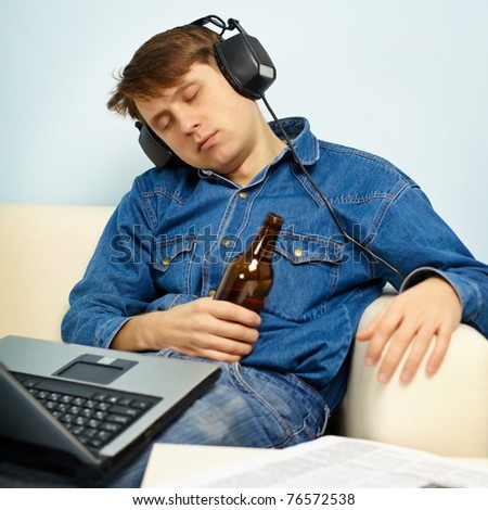 A young man fell asleep at home on the couch with a beer