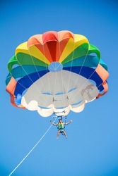 a young man flies on a parachute , blue sky and a parachute otd?h the sea and entertainment