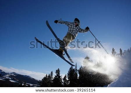 A young man flies through the air after hitting a ski jump in the back country.